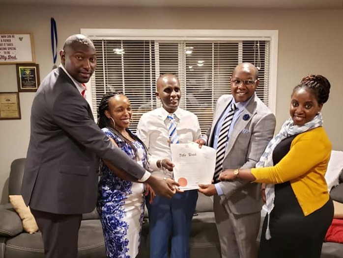 Photo Caption: Username Investments Team issuing a title deed to a client in the USA
